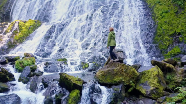 Woman Climbing Over Rocks at Foot of Waterfall video