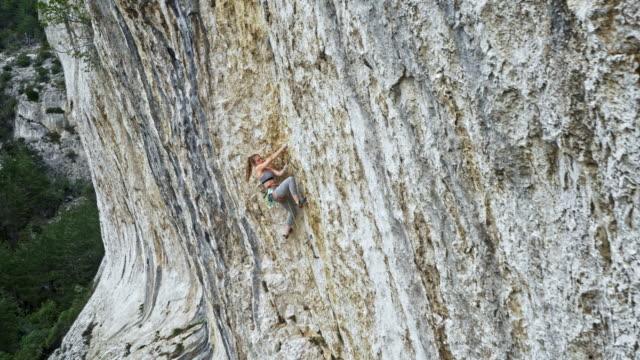 vídeos y material grabado en eventos de stock de antena mujer subiendo un acantilado - escalada en rocas