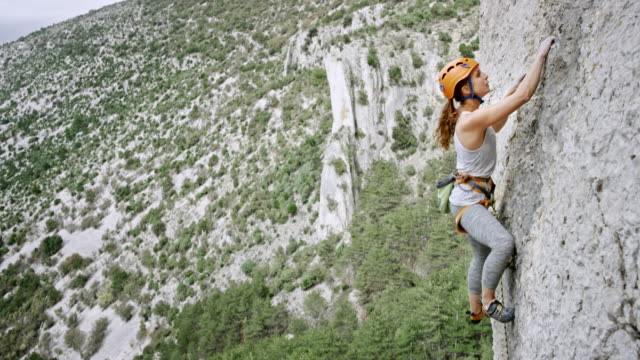 Woman climbing up the rocky wall of a cliff video