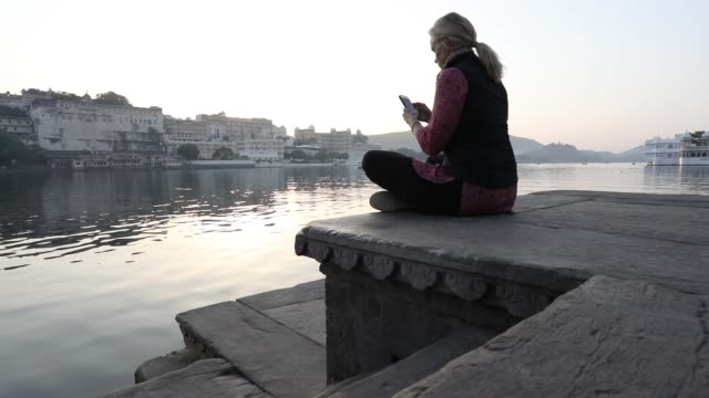 woman climbs onto ghat above lake and floating palace - ghat filmów i materiałów b-roll