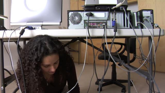 vídeos y material grabado en eventos de stock de mujer escala para fijar ordenador de escritorio - cable