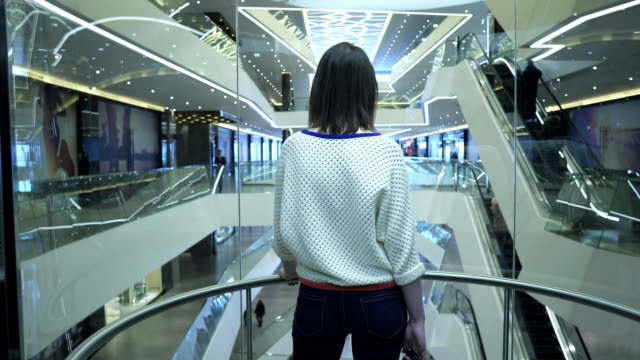 Woman climbs up on the elevator in a shopping center, view from the back