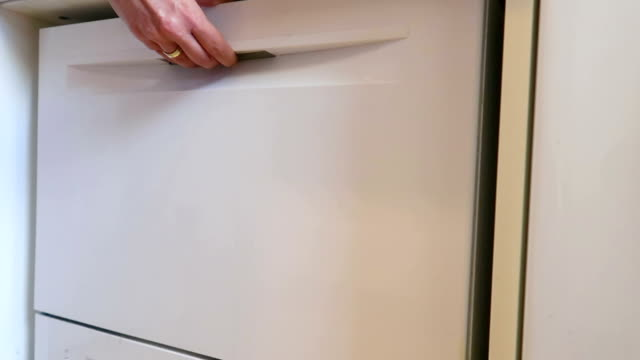 Woman closing a dishwasher - Stock video Female hand closing full dishwasher dishwasher stock videos & royalty-free footage