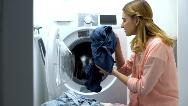 kadın yıkandıktan sonra kokuşmuş giysilerburun kapatma, düşük kaliteli sabun tozu - kokulu stok videoları ve detay görüntü çekimi