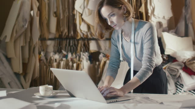woman clothing designer is working on a laptop while leaning on a studio table. - tailor working video stock e b–roll