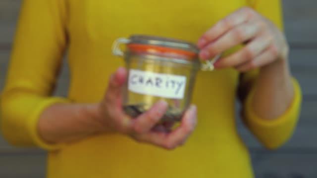 vídeos de stock e filmes b-roll de woman collecting money for charity and holds jar with coins. - coração fraco
