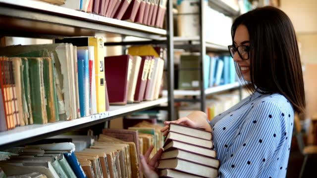 die studentin der frau, die in der bibliothek arbeitet, hält eine reihe von büchern in händen, die schlau aussehen. bücherregale in der bibliothek. - literatur stock-videos und b-roll-filmmaterial