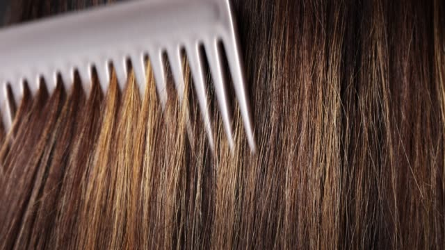 Woman combing her long dyed hair Young woman styling her long straight shiny dyed hair with comb, visible color layers highlights, care concept highlights hair stock videos & royalty-free footage