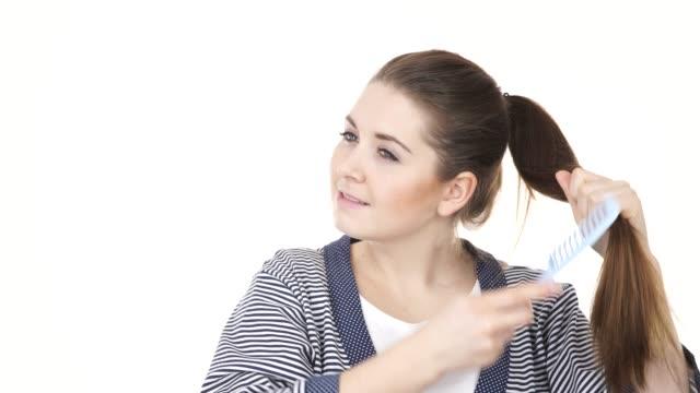 stockvideo's en b-roll-footage met vrouw kammen haar lang haar met blauwe kam 4k - paardenstaart haar naar achteren