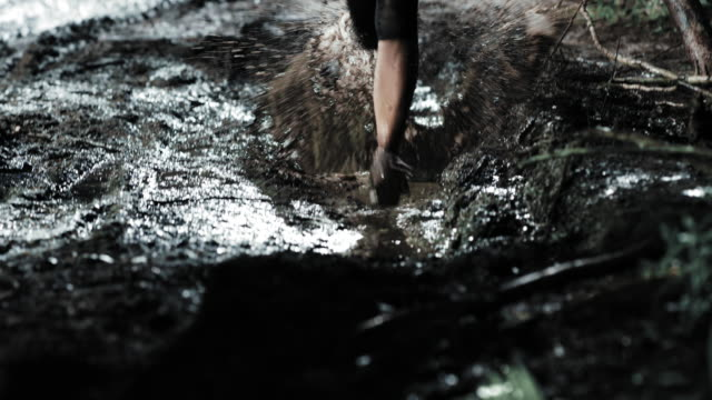 TD Woman competing in a night trail run running across a puddle Medium tilt down shot of a female runner competing in a trail run at night running across a puddle on the forest trail. The marathon competition was created and specially organised just for the shooting. It is not a shot from the official event. mud stock videos & royalty-free footage