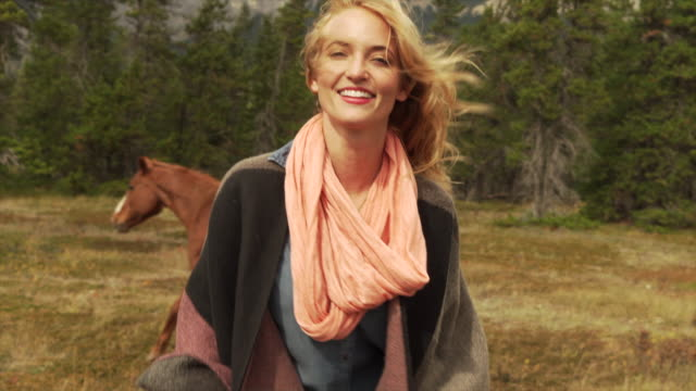 woman connects with horses, in mountain meadow - spettinato video stock e b–roll