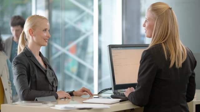 Woman consulting a female bank teller video
