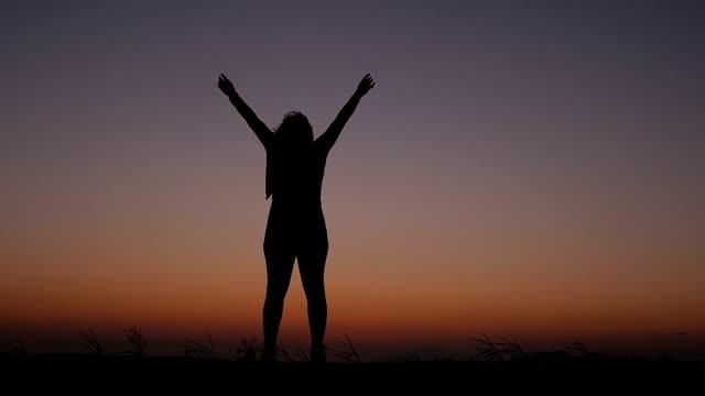 vidéos et rushes de femme contemple le ciel au coucher du soleil, et ouvre les bras :  liberté, de bien-être - armement