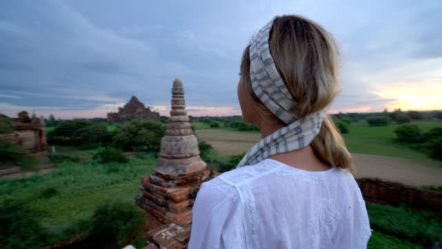 Woman contemplating on top of ancient temple in Myanmar. Woman contemplating on top of ancient temple in Myanmar. Young woman standing on top of Buddhist temple in Bagan. Traveller woman contemplating at sunrise bagan stock videos & royalty-free footage