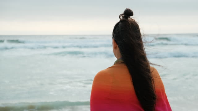 Woman Contemplating The Ocean Standing on a Beach