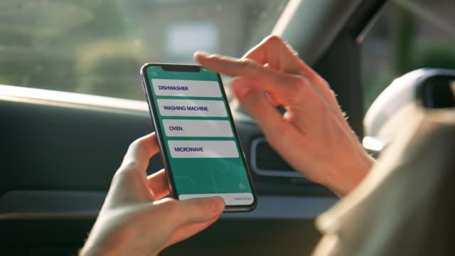 donna che controlla gli elettrodomestici attraverso lo smartphone - elettrodomestico attrezzatura domestica video stock e b–roll