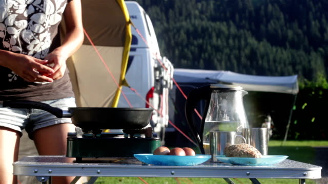 Woman cooking breakfast in camping video