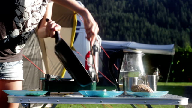 Woman cooking eggs and making tea in camping video