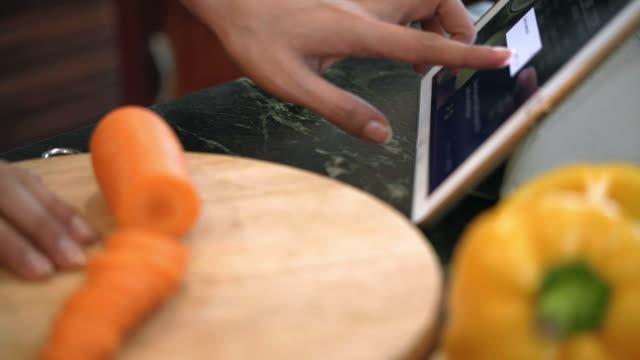 woman cooking following recipe from internet - podążać za czynność ruchowa filmów i materiałów b-roll
