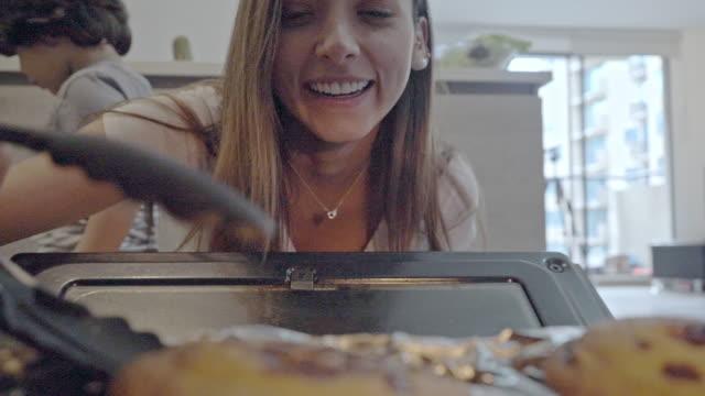 frau kocht im küchenofen, während ihr sohn auf covid-19 unter quarantäne gestellt wird - lateinische schrift stock-videos und b-roll-filmmaterial