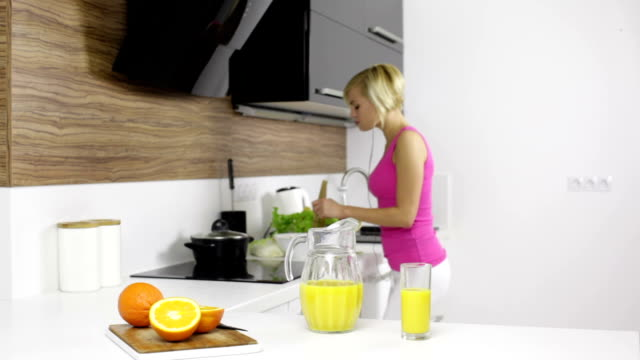 woman cooking on modern kitchen dancing listen to music mixing vegetables salad and drinking orange juice happy smile, girl at home video