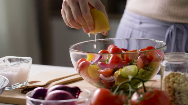 woman cooking vegetable salad with lemon at home