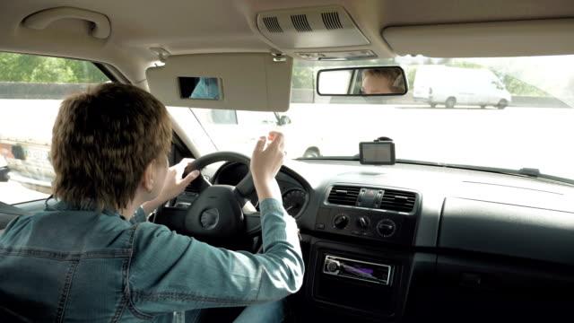 Woman corrects make-up in a car sun visor mirror video