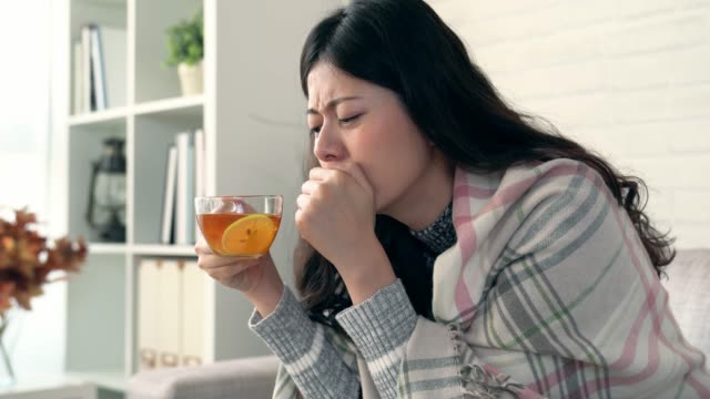 woman coughing and drinking hot lemon tea - flu shot стоковые видео и кадры b-roll