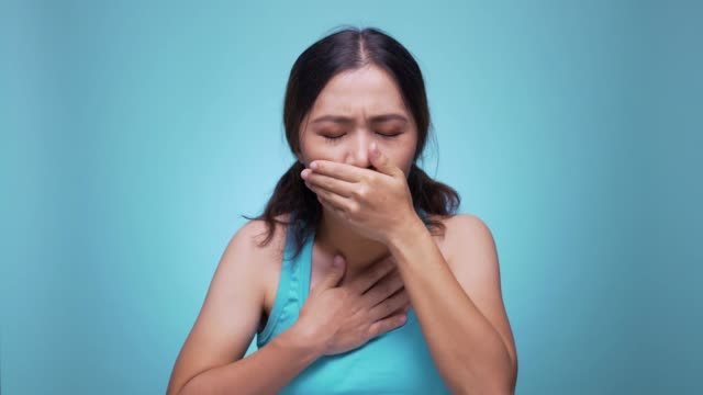 Woman coughing on isolated blue background 4k Woman coughing on isolated blue background 4k coughing stock videos & royalty-free footage