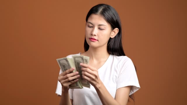 woman counting cash isolated. asian woman in white t-shirt counting dollar. rich woman concept. - bonus video stock e b–roll
