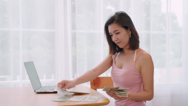 Woman counting dollars on the table beside the computer desk in the living room.
