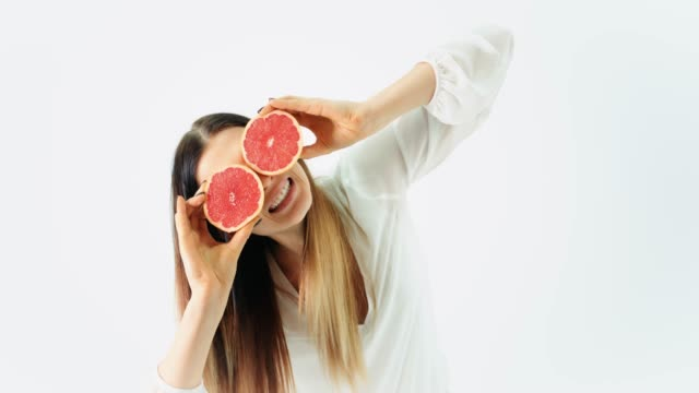 Woman Covering Her Eyes with Two Grapefruits