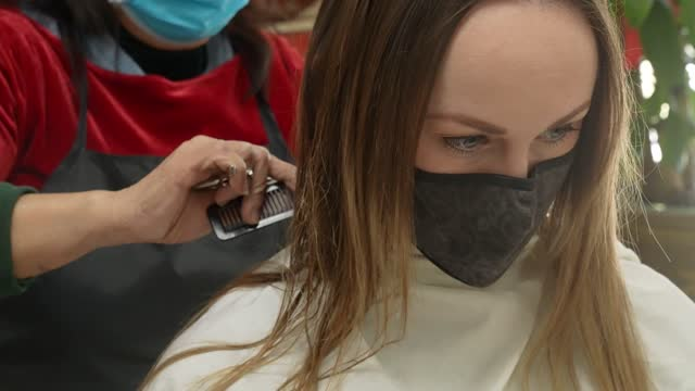 woman covid mask getting haircut front view This video shows a front view of a woman wearing a protective COVID face mask covering getting her hair cat at a salon. hairstyle stock videos & royalty-free footage