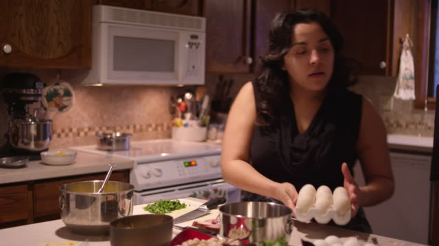 A woman cracks an egg into a bowl, in the kitchen with her son and husband - vídeo