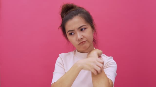 Woman cratching her hand on isolated pink background 4k