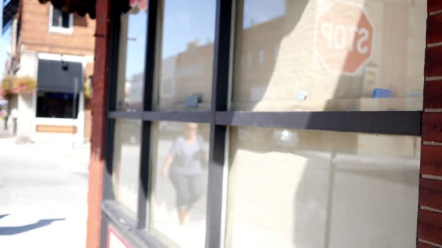 Woman crosses intersection near papered over windows of storefront - vídeo