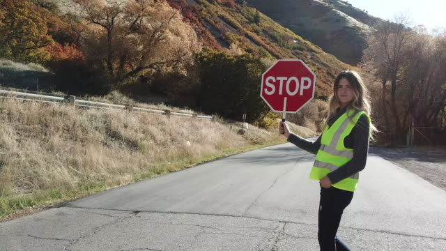 Woman crossing guard stopping traffic in canyon road video