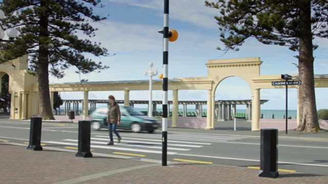 woman crossing street by napier soundshell - art deco architecture stock videos & royalty-free footage