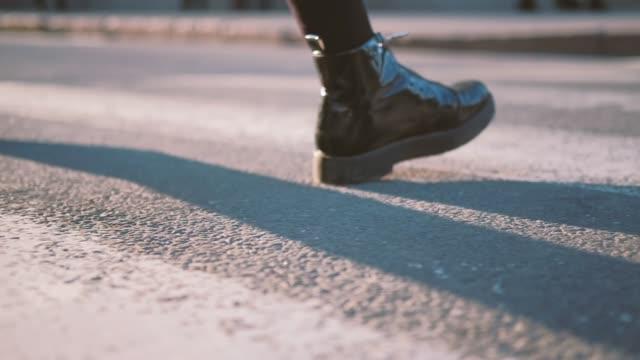 woman crossing street crosswalk black patent boots