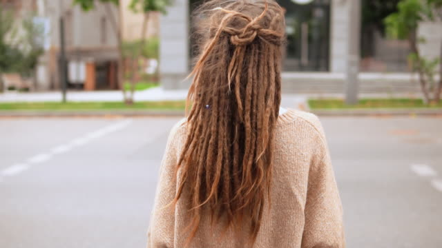 woman crossing the road back view girl with dreadlocks walking on crosswalk hair fluttering in the wind locs hairstyle stock videos & royalty-free footage