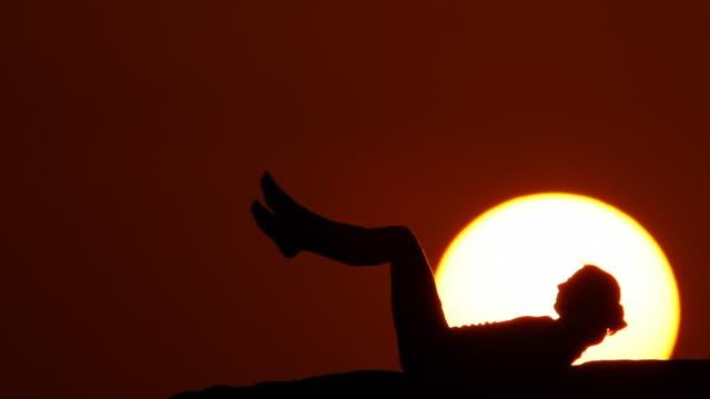 vidéos et rushes de femme marchant au coucher du soleil - allongé sur le dos
