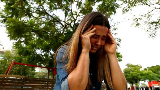 woman crying in a park - wine filmów i materiałów b-roll
