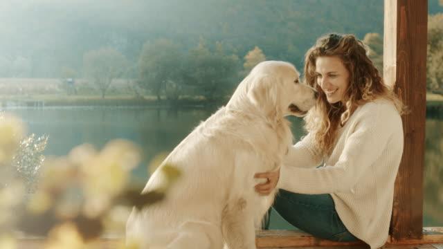 Woman cuddling and kissing a dog