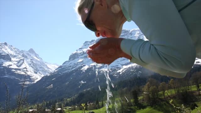 frau becher hände aus bergbach trinken - kanton bern stock-videos und b-roll-filmmaterial