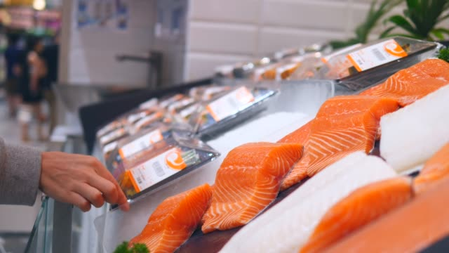 vídeos y material grabado en eventos de stock de mujer cliente eligiendo salmón fresco en el supermercado - pescado y mariscos