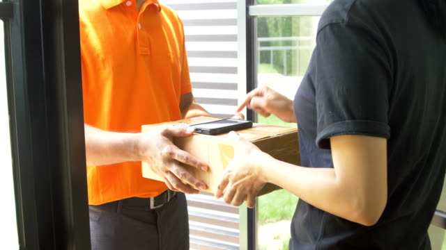 Woman customer receiving package from delivery man at the door