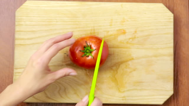 frau schneidet eine tomate auf einem holzbrett. ansicht von oben - vegetarisches gericht stock-videos und b-roll-filmmaterial