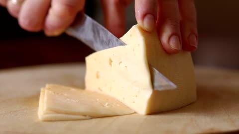 vídeos y material grabado en eventos de stock de una mujer cortes de queso en un corte de tablero, primer plano. - cortar