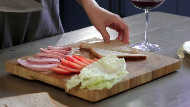 kvinna skär klubb smörgås i en halv med kniv på en träskiva i köket, vilket gör av fastfood hemma, är kocken matlagning smörgås. närbild. flickans händer skär bröd för en smörgås, frukost - cheese sandwich bildbanksvideor och videomaterial från bakom kulisserna