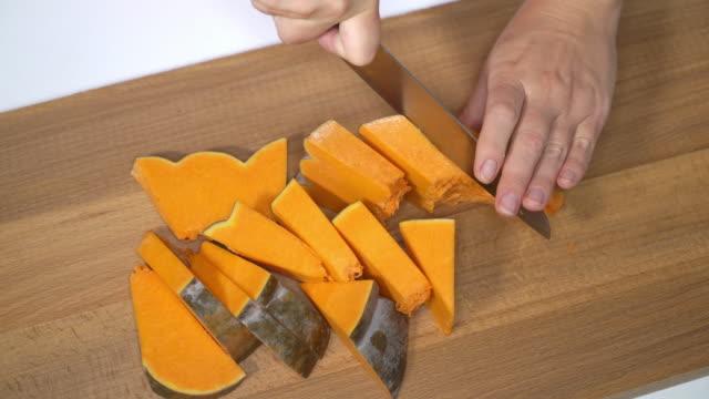 女人切成塊的烤箱中烘烤的新鮮的南瓜泥 - pumpkin pie 個影片檔及 b 捲影像